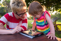 mom and her little daughter using tablet computer - PhotoDune Item for Sale