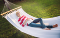 woman reading a book while relaxing on hammock - PhotoDune Item for Sale
