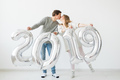 New 2019 Year is coming concept - Happy young man and woman are holding silver colored numbers on - PhotoDune Item for Sale