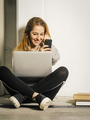 Young woman laughing at her smartphone - PhotoDune Item for Sale