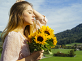 Young woman enjoying the sunlight holding sunflowers - PhotoDune Item for Sale