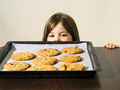 Young girl looking at a tray of fresh baked cookies - PhotoDune Item for Sale