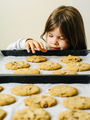 Young girl grabbing cookies from a baking tray - PhotoDune Item for Sale