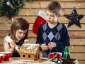 Brother and sister decorating gingerbread house - PhotoDune Item for Sale