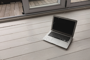 High angle view of laptop kept on a wooden surface at home