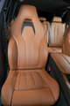 Red perforated leather car seat with the unfocused car interior in the background - PhotoDune Item for Sale