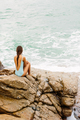 Beautiful girl in blue swimsuit sit on big stone. - PhotoDune Item for Sale