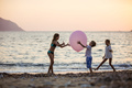 Children playing with huge pink balloon on beach at sunset - PhotoDune Item for Sale