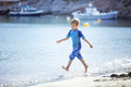 Happy young boy running along water edge  and making splashes - PhotoDune Item for Sale