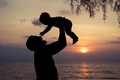 Father and baby son  playing on the beach at the sunset time. - PhotoDune Item for Sale