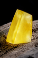 Natural amber. A piece of yellow opaque natural amber on large piece of dark stoned wood - PhotoDune Item for Sale