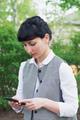 brunette caucasian businesswoman touch smartphone walking in park - PhotoDune Item for Sale