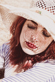 Redhead model protecting herself from sun with a hat in summer - PhotoDune Item for Sale