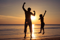Father and son  playing on the beach at the sunset time. - PhotoDune Item for Sale
