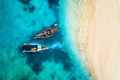 Aerial view of the fishing boats in clear blue water at sunset - PhotoDune Item for Sale