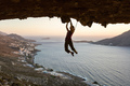 Female rock climber on challenging route in cave at sunset - PhotoDune Item for Sale