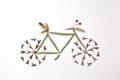 Pattern of leaves and pine seeds in the form of a bicycle on a gray background with copy space - PhotoDune Item for Sale