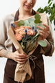 Smilling girl florist with creative bouquet from fresh flowers roses in a paper on a light - PhotoDune Item for Sale