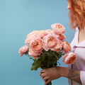 Gentle pink roses in the hands of a girl with a tattoo on a blue background with copy space for text - PhotoDune Item for Sale
