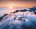 Passenger airplane is flying over clouds at sunset - PhotoDune Item for Sale