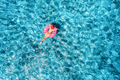 Aerial view of young woman swimming on the swim ring in blue sea - PhotoDune Item for Sale