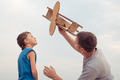 Father and son playing with cardboard toy airplane - PhotoDune Item for Sale