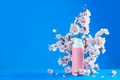 Cherry blossom cosmetics header. Pink creme tube with spring flowers on a sky blue background with - PhotoDune Item for Sale