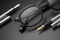 Black plastic eye glasses with two fountain pens on dark background - PhotoDune Item for Sale
