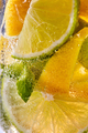 Macro photo of sliced lemon and lime with a leaf of mint and bubbles in glass. Cool drink mojito - PhotoDune Item for Sale