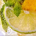 Macro photo of fresh slices of green lime, yellow lemon and mint leaf with bubbles in a glass - PhotoDune Item for Sale