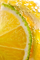 Juicy slices of ripe lemon and lime with bubbles in a glass of water. Macro photo of refreshing - PhotoDune Item for Sale