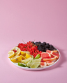 Set of different citrus fruits and berries in a plate presented on a pink background with copy space - PhotoDune Item for Sale