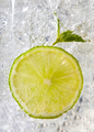 Macro photo of a piece of lime and mint leaf in a glass with ice and bubbles. Cold summer drink - PhotoDune Item for Sale