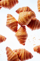 Falling fresh french croissants with crumbs on a light background - PhotoDune Item for Sale