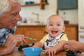 Grandfather feeding happy little boy - PhotoDune Item for Sale
