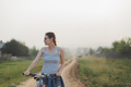 caucasian woman standing with bicycle in countryside road - PhotoDune Item for Sale