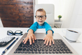 Cute child with glasses using a laptop - PhotoDune Item for Sale