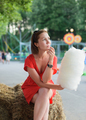 young adult woman sitting on bale of hay and holding white cotton candy at amusement park - PhotoDune Item for Sale