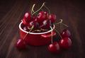 red bowl full of cherries on wood - PhotoDune Item for Sale