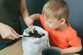 mother and little son take soil from bag to metal flower pot on table - PhotoDune Item for Sale