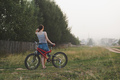 young woman standing with bicycle countryside near garden in village - PhotoDune Item for Sale
