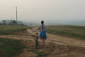 young woman walking with bike, looking on village in evening fog - PhotoDune Item for Sale
