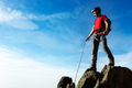 A climber helps his partner to reach the summit of a mountain pe - PhotoDune Item for Sale