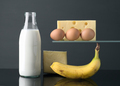 milk bottle eggs cheese and banana on gray background - PhotoDune Item for Sale