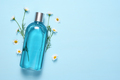 Cosmetic bottle and chamomile flowers on blue table top view with text space - PhotoDune Item for Sale