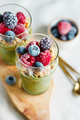 Top view on portions of chia pudding with matcha tea, organic granola, frozen berries in glasses.  - PhotoDune Item for Sale