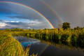 Amazing double rainbow over the small rural river. - PhotoDune Item for Sale