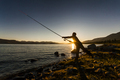 Silhouette of a fisherman at sunset. Fishing on mountain lake - PhotoDune Item for Sale