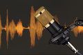 Gold colored condenser microphone over waveform. - PhotoDune Item for Sale