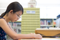 Young Asian student reading a book in library - PhotoDune Item for Sale
